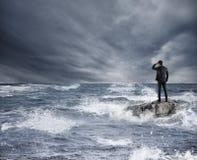 Biznesmen patrzeje dla przyszłości podczas burzy w morzu Pojęcie kryzys gospodarczy i problem Zdjęcia Royalty Free
