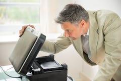 Biznesmen patrzeje fotokopii maszynę zdjęcie royalty free