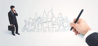 Biznesmen patrzeje gotowego rysującego miasto na ścianie Zdjęcia Stock