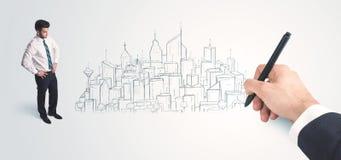 Biznesmen patrzeje gotowego rysującego miasto na ścianie Fotografia Stock