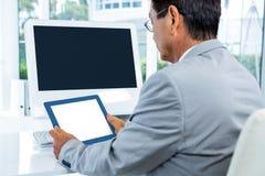 Biznesmen patrzeje jego pastylkę Zdjęcia Royalty Free