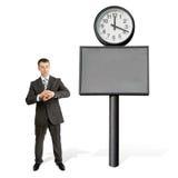 Biznesmen patrzeje jego rękę blisko dużego zegaru zdjęcia royalty free