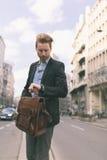 Biznesmen patrzeje jego wristwatch w ruchliwie mieście obraz stock