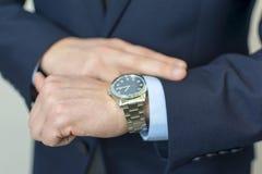 Biznesmen patrzeje jego zegarek na jego ręce obraz royalty free