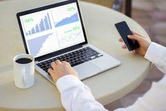 Biznesmen patrzeje laptopu ekran z biznesowymi mapami zdjęcia royalty free