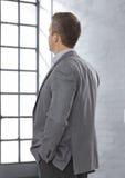 Biznesmen patrzeje nadokienną twarz widoczną Zdjęcia Royalty Free