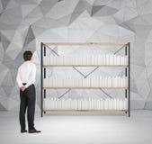 Biznesmen patrzeje półka na książki Zdjęcia Royalty Free