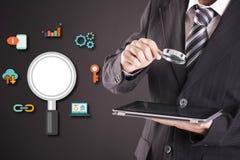 Biznesmen patrzeje pastylkę z powiększać - szkło Ikony analiza Zdjęcia Stock