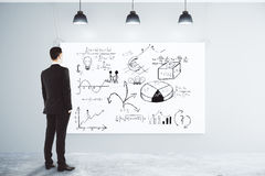 Biznesmen patrzeje plakat z biznesowym planu pojęciem o obrazy stock