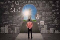 Biznesmen patrzeje przez kluczowej dziury z SEO doodle na blackboard Zdjęcia Stock