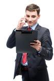 Biznesmen patrzeje w falcówce i opowiada na telefonie Obraz Royalty Free