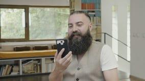 Biznesmen patrzeje wideo na jego smartphone i ma radosną podporową reakcję robi zwycięstwo gestowi z jego rękom zdjęcie wideo