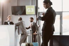 biznesmen patrzeje zegarek podczas gdy czekający lot zdjęcia stock