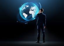 Biznesmen patrzeje ziemskiego kula ziemska hologram Zdjęcia Royalty Free