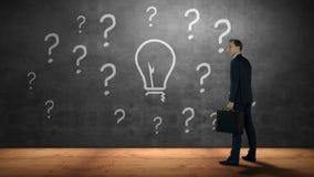 Biznesmen patrzeje znaki zapytania i żarówkę zbiory