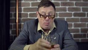 Biznesmen pije alkohol indoors z ściana z cegieł zdjęcie wideo
