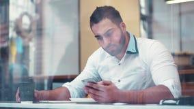 Biznesmen pije kawę okno w kawiarni i ma rozmowę telefoniczną, po końcówki rozmowa mężczyzna zdjęcie wideo