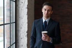 Biznesmen pije kawę w biurowej trwanie pobliskiej nadokiennej patrzeje kamerze obraz stock