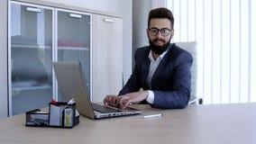 Biznesmen pisać na maszynie na laptopie i patrzeje kamerę z uśmiechem zdjęcie wideo