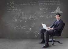 Biznesmen pisać na maszynie na jego laptopie z maths równaniami na ścianie Zdjęcie Royalty Free