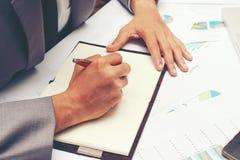 Biznesmen pisze biznesowym raporcie na pustym notatniku z czerwonym piórem na biurka biurze Biznesowy pojęcie: Zdjęcie Stock