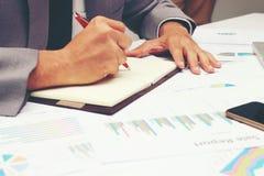 Biznesmen pisze biznesowym raporcie na pustym notatniku z czerwonym piórem na biurka biurze Biznesowy pojęcie: Obraz Stock