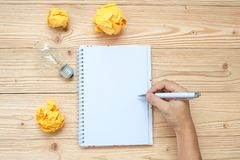 Biznesmen pisze na notatniku z lightbulb i rozdrobniącym papierem na drewnianym stole Pomysł, Kreatywnie, innowacja, rozwiązanie, zdjęcia royalty free