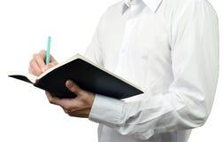 Biznesmen pisze notatce na jego książce obrazy stock