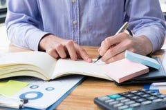 Biznesmen pisze notatce na notatniku przy biurowym biurkiem mężczyzna pisze mem Zdjęcie Stock