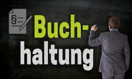 Biznesmen pisze z kredowym Buchhaltung w niemieckiej księgowości na blackboard zdjęcie stock
