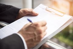 Biznesmen podpisuje przy szyldowym papierem, Biznesowy zgoda przeciw fotografia stock