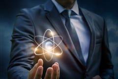Biznesmen pokazuje atom Zdjęcia Royalty Free