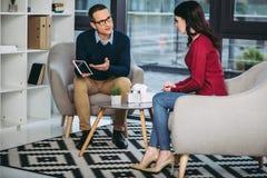 Biznesmen pokazuje bizneswomanowi cyfrową pastylkę zdjęcie royalty free