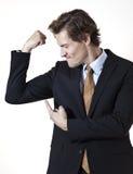 Biznesmen pokazuje daleko mucsles Fotografia Stock