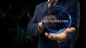Biznesmen pokazuje pojęcie holograma outsourcing na jego ręce zdjęcie royalty free