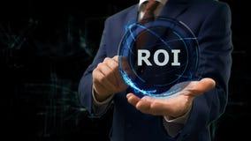 Biznesmen pokazuje pojęcie holograma ROI na jego ręce Fotografia Stock
