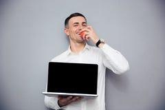 Biznesmen pokazuje pustego laptopu ekran i je jabłka Zdjęcia Stock