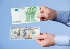 Biznesmen porównuje sto dolarów i sto euro Zdjęcia Stock