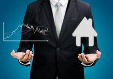 Biznesmen pozyci postury ręki chwyta wykres i dom odizolowywający Obrazy Stock