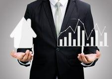 Biznesmen pozyci postury ręki chwyta wykres i dom odizolowywający Zdjęcie Stock