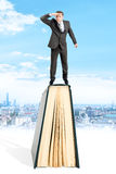 Biznesmen pozycja na książkowym i patrzeć daleko od obraz stock