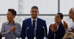 Biznesmen pozycja na podium z jego kolegami w biznesowym konwersatorium 4k zbiory