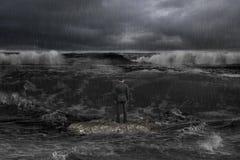 Biznesmen pozycja na rockowych okładzinowych nadchodzących fala z ciemnym oce Fotografia Stock