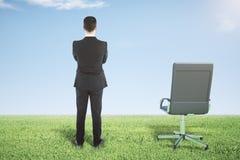 Biznesmen pozycja na zielonej trawie i spojrzeniach daleko od Obraz Royalty Free