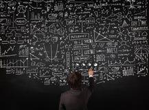 Biznesmen pozycja przed patroszonymi mapami na blackboard zdjęcie stock