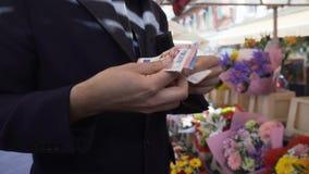 Biznesmen pozycja przy kwiatu bukieta sklepem i odliczającym pieniądze w jego portflu zdjęcie wideo