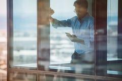 Biznesmen pozycja wśrodku budynku biurowego i używać smartphone Zdjęcie Royalty Free