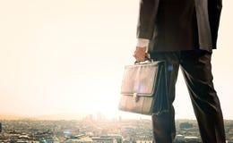 Biznesmen pozycja z plecy przeciw miastu zdjęcia stock