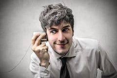 Biznesmen próbuje słuchać coś zdjęcie royalty free