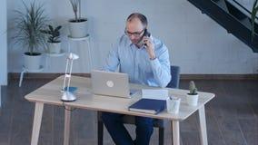 Biznesmen praca na komputerze podczas gdy opowiadający na mądrze telefonie Zdjęcia Stock